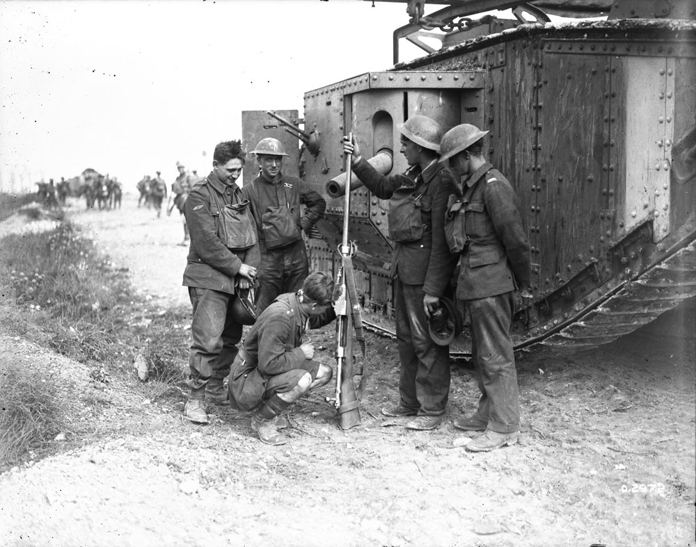 Tank Officer and Men interested in an anti-tank rifle captured by Canadians. Battle of Amiens. August, 1918.